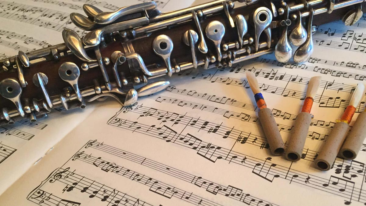 A photograph of an oboe on a sheet of music with some reeds next to it